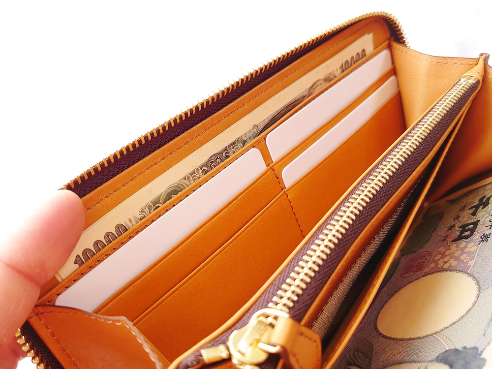 crafsto(クラフスト)ブライドルレザー「ラウンドファスナー長財布」ダークブラウン 振両サイドのフリーポケットにお札を入れる